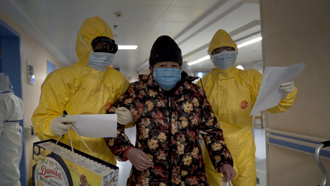 Two men in hazmat suits leading an old woman down a corridor.